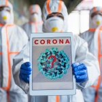 People with protective suits and mask respirators outdoors, coronavirus pandemic concept. Image credit: Jozef Polc / 123rf