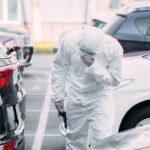 asian epidemiologist in hazmat suit and respirator mask inspecting vehicles on parking lot. Coronavirus pandemic illustration. Image credit: lightfieldstudios / 123rf
